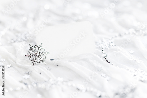 White holiday background with sparkling silver snowflakes, Christmas decorations and empty piece of paper for your text. Clear visit card on New Year fabric background.