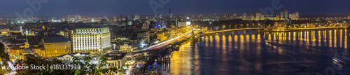 In de dag Kiev Kyiv (Kiev) city, the capital of Ukraine at night beside the Dnipro (Dniepr) river with reflection in water