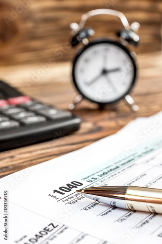 Tax forms with clock, pen and calculator on the office wooden table. Top view. Business and tax concept. - 181336718