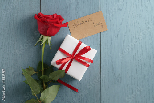 red rose on blue wood table with gift box and valentines day paper card
