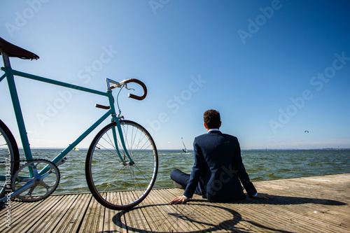 Young man with bike on pier