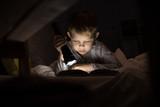 Portrait of cute little boy reading in bed with flashlight in dark room, enjoying fairytales - 181341154