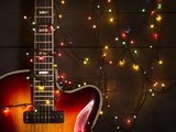 Fototapety Old electric guitar with a lighted garland on a dark background. Greeting, Christmas, New Year greeting card. Copy space.