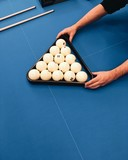Russian billiard balls in triangle pyramide on blue table in man's hands