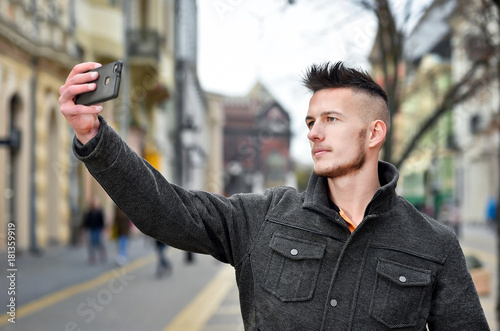 young man taking selfie photo in autumn on street