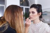 makeup artist applying lip contour with pencil