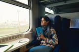 Pretty woman traveling by train sitting near window. Enjoying travel