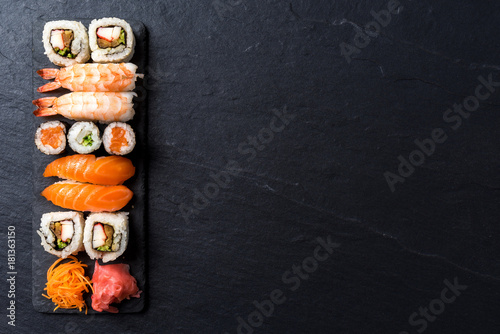 Staande foto Sushi bar Overhead shot of Japanese sushi on black concrete background