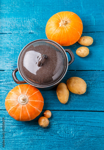 Fototapeta Picture on top of iron pot with lid, vegetables, potatoes, pumpkin