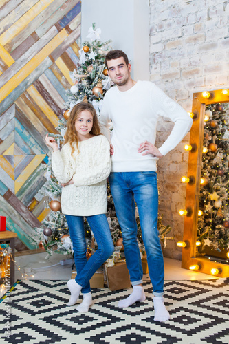 Christmas concept, fashion. father and daughter in elegant pullover posing in luxurious apartments decorated for Christmas. Hairstyle.