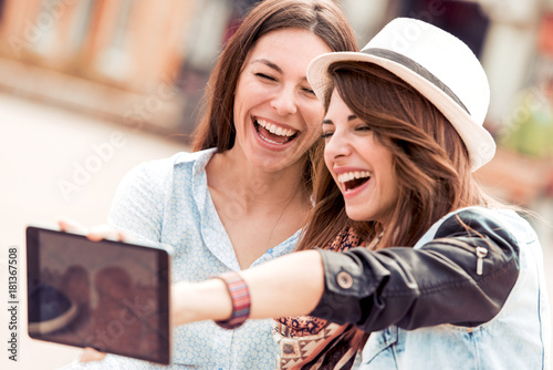 Two friends taking a selfie in the city Poster