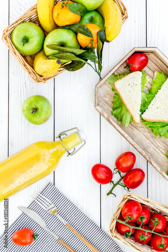 Healthy food for picnic. Sanwiches, fruits, vegetables, juice on tablecloth on white wooden background top view