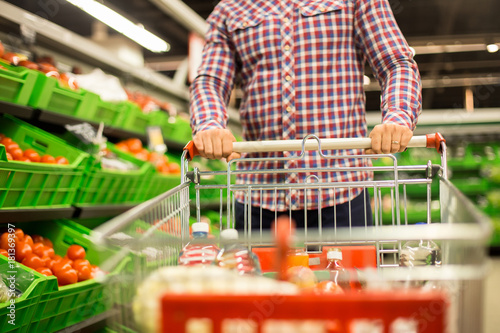 Front view closeup of man pushing shopping cart with food while buying groceries in supermarket