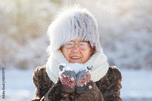 Old woman walking at winter park
