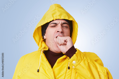 Fatigue sleepy man has much work, yawns, dreams about long healthy sleep, poses against blue background, dressed in fashionable anorak Plakát