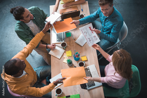 Creative teamwork. Top view of excited young workers are transferring documents to each other while sitting at table. They are expressing gladness while working together