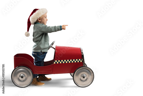 Child that play with his car waits for Santa Claus