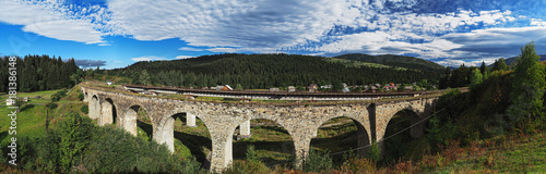 Panorama of the old stone austrian bridge through the river at the Karpatian mountains