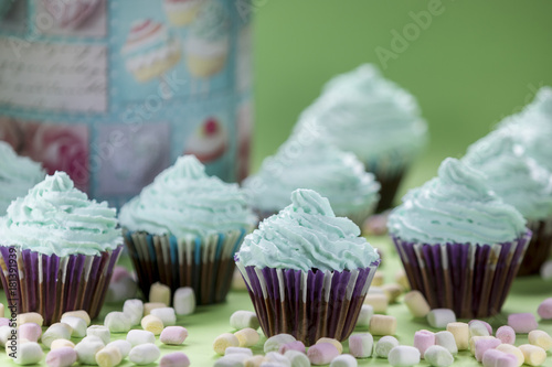 Cupcakes with minis marshmallows on green background Poster