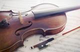 Violine mit Bogen auf Notenblättern - 181392500