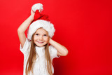 Happy smiling girl in Christmas cap and white pullover on a red background. Merry Christmas. Happy New Year - 181393993