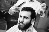 Fryzjer rozpyla wodę na włosach klienta w nowoczesnym salonie fryzjerskim