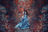 Mysterious sorceress in a beautiful blue dress. Her hair and dress are fluttering in the wind. Background bright, autumn, fiery forest with cold tones. Artistic Photography - 181398528