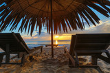 Sun loungers with umbrella on the beach, sunrise - 181399700