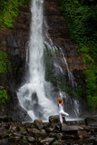 Woman practices yoga at Gitgit waterfall on Bali in indonesia - 181400139