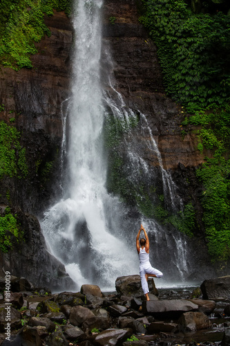 Fototapeta Woman practices yoga at Gitgit waterfall on Bali in indonesia