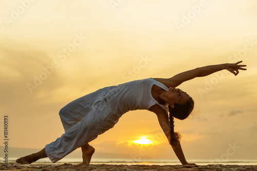 Poster Woman practices yoga at the seashore at sunset on Bali in indonesia