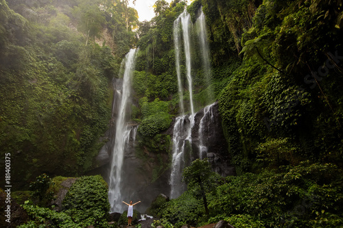 Woman in white dress at the Sekumpul waterfalls in jungles on Bali island, Indonesia - 181400375