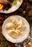 Dumplings stuffed with cabbage and mushrooms on a white plate, located on a wooden Christmas table, top view. Traditional Christmas eve dish in Poland - 181403512
