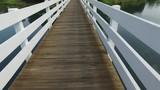 Walking over a walkway bridge over water - 181404704