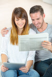 couple happy with the news on the newspaper - 181409101