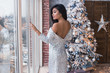 Sexy and elegant young girl in sparkle dress with a sexy bag. Asian girl celebrate a New Year party with a beautiful Christmas Tree with a glass of champagne. Christmas party in a white studio