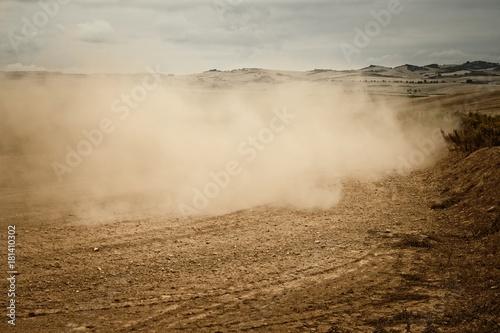 Foto Murales carretera de tierra con una nube de polvo despues de pasar un vehiculo