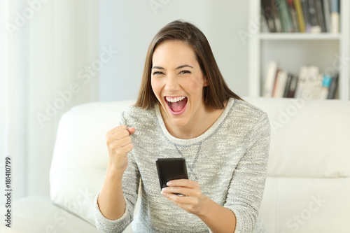 Excited woman holding phone looking at you Poster