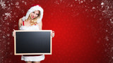 Weihnachtsfrau mit leerer Kreidetafel vor rotem Weihnachtshintergrund