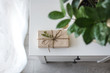gift wrapped in kraft paper tied with string decorated with a branch with green leaves lies on a white bedside table