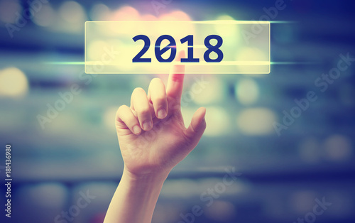 2018 concept with hand pressing a button on blurred abstract background