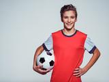 smiling teen boy in sportswear holding soccer ball - 181445113