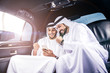 Two arabic businessmen inside their company limousine