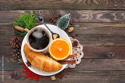 Papiers peints Cafe Christmas and New Year background with continental breakfast - cup of hot coffee with cinnamon, fresh orange and croissant. Decorations - snowflake, crochet napkin, pine cones.