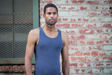 Portrait of young handsome African American man in tank top against brick wall - 181449315