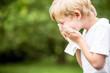 Kind mit Allergie beim Niesen in Taschentuch
