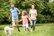 Familie mit Tochter und Hund spielen im Garten