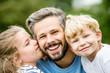Glücklicher Vater mit zwei Kindern lacht