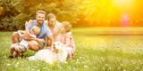 Glückliche Familie mit Kinder und Hund im Garten - 181450948