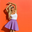 Beautiful Blond Woman In Sunglasses, Violet Mini Skirt And White Tank Top Is Posing With Arms Raised